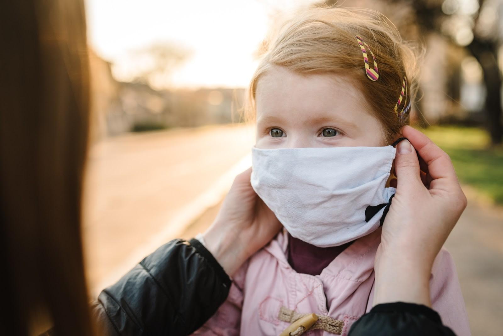 Mãe protegendo a filha colocando mascara nela