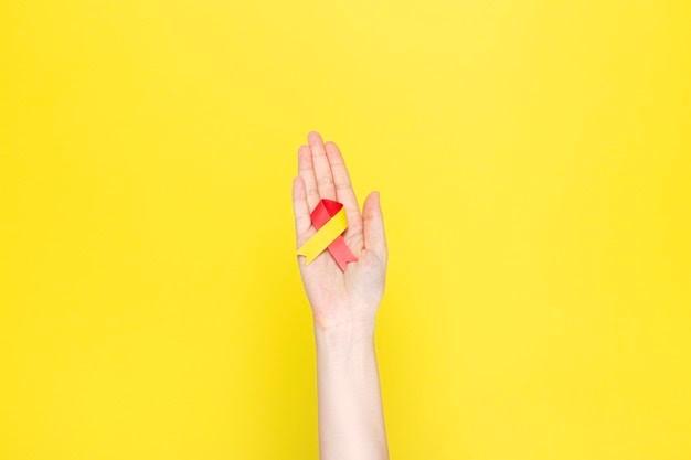 Uma mão segurando o laço amarelo e vermelho