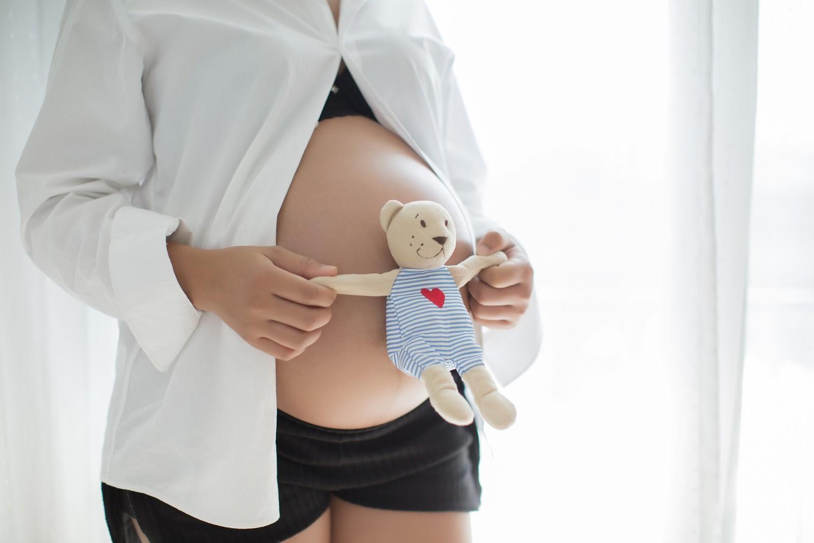 Mulher gravida segurando um ursinho