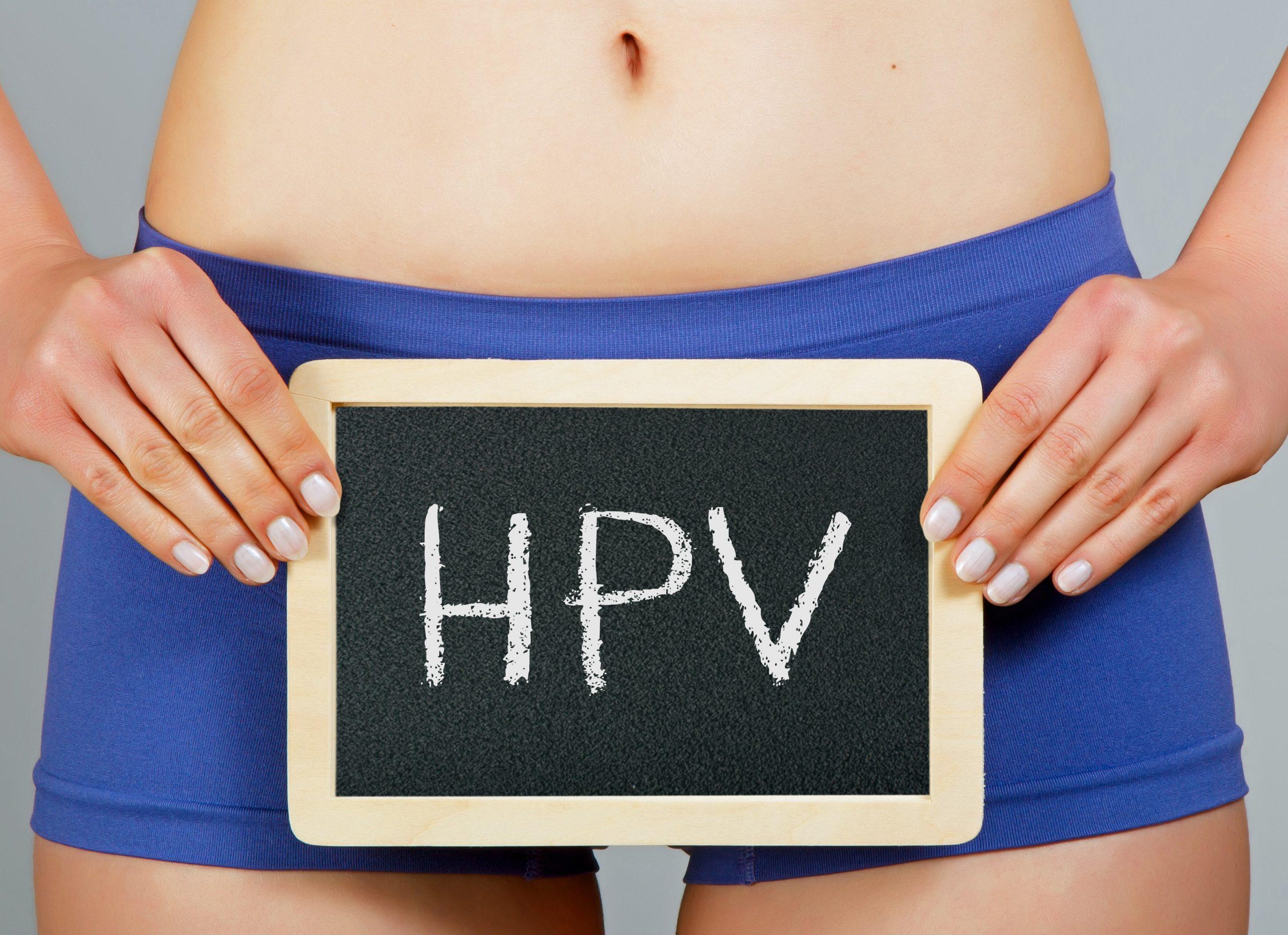 Mulher segurando uma plaquinha escrita HPV